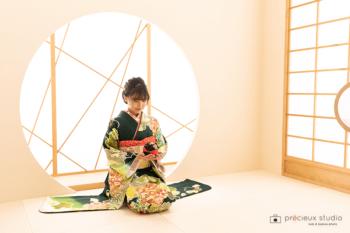 緑の晴れ着の女性 成人式記念写真 和室で座り姿