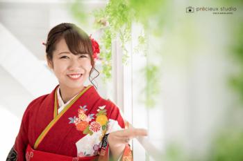 赤い晴れ着の女性 成人式記念写真 笑顔