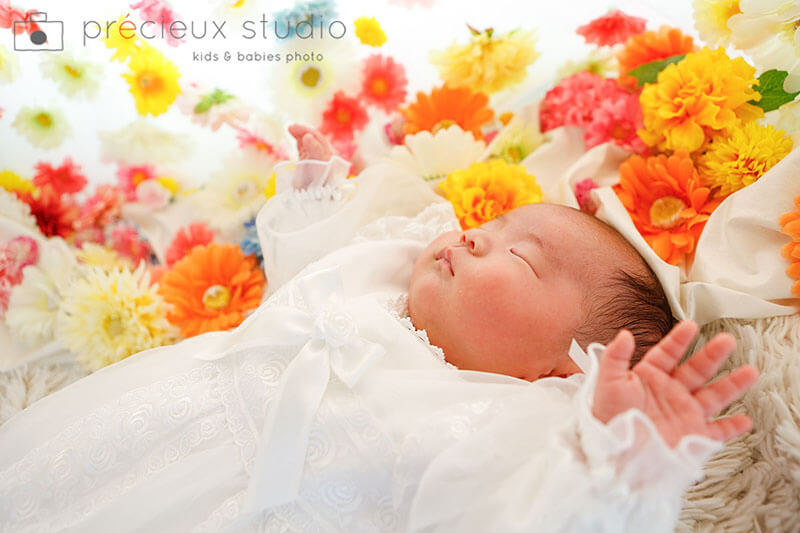お花と寝ている赤ちゃんのお宮参り記念写真