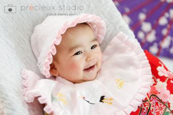 お宮参りの記念写真 ピンクのスタイの赤ちゃん