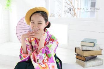 女の子の卒業袴 小学校卒業記念写真 花柄の着物と黄色のニット帽 和傘と一緒に プレシュスタジオ撮影写真
