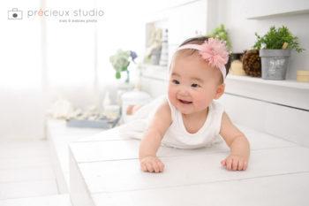 ピンクの花のヘアバンドを着けたハーフバースデーの女の子 プレシュスタジオ撮影写真