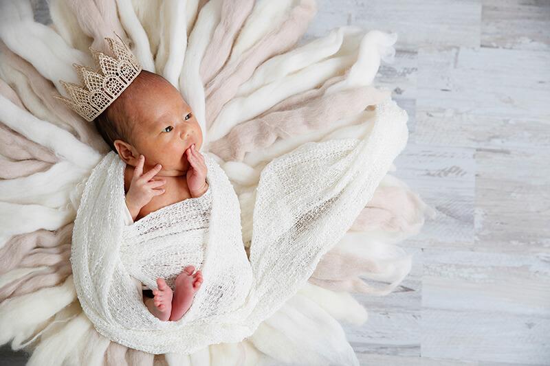 ニューボーンフォト撮影 王冠をかぶったおくるみの赤ちゃん
